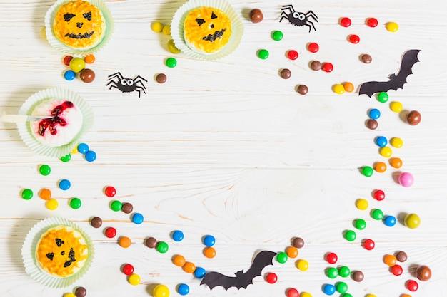 Mini muffins perto de pequenos doces, morcegos e aranhas