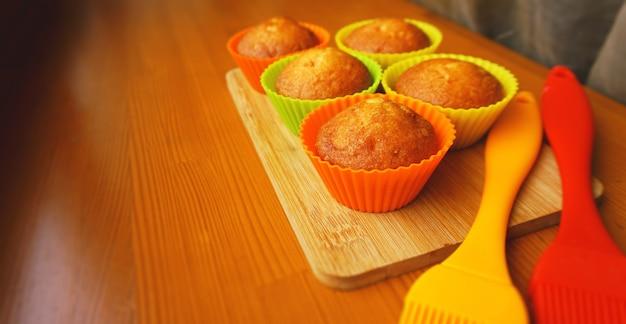 Mini muffins simples em assados coloridos de silicone. cupcakes de silicone para assar cupcakes e pincéis de silicone. cozinha e conceito de cozinha em fundo de madeira