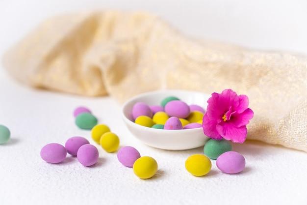 Mini ovos coloridos dentro de uma tigela com uma flor rosa sobre uma mesa branca com pano de cozinha bege