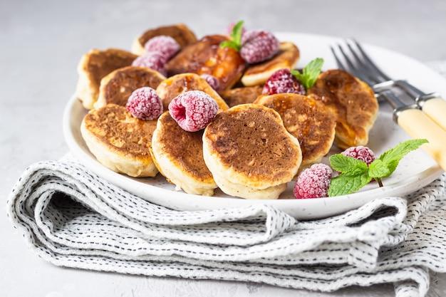 Mini panquecas com framboesas, hortelã e geléia. panquecas cozidas no café da manhã na cozinha de casa.