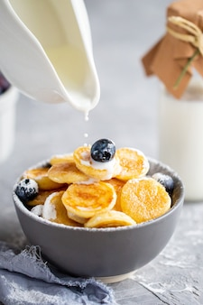 Mini panquecas de aveia. panquecas com mirtilos e morangos.panqueca mingau, mini panquecas em uma tigela com leite e xarope de bordo.