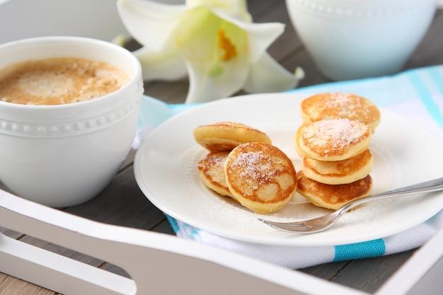 Mini panquecas holandesas chamadas poffertjes, polvilhadas com açúcar de confeiteiro