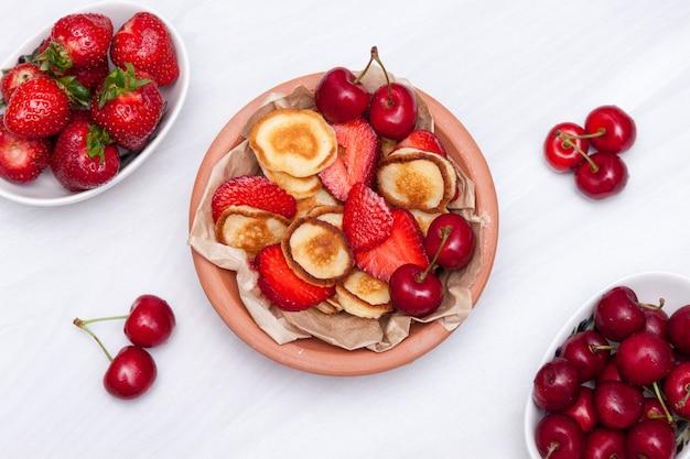 Mini panquecas minúsculas com mirtilos e cerejas em fundo branco de madeira. conceito de comida na moda. postura plana.