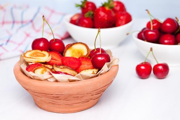 Mini panquecas minúsculas com mirtilos e cerejas em fundo branco de madeira. conceito de comida na moda.