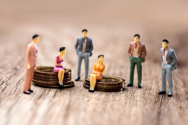 Mini pessoas com moedas na mesa