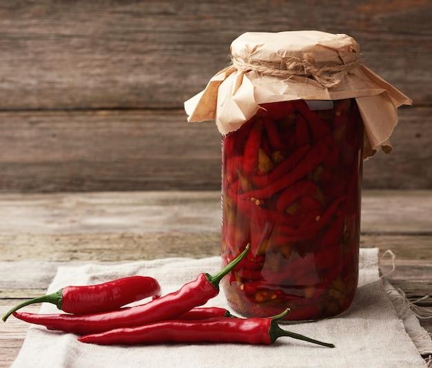Mini pimenta em conserva vermelha em uma jarra de vidro e frutas frescas nas proximidades