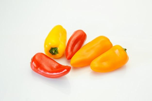 Mini pimentas doces coloridas isoladas no fundo branco.