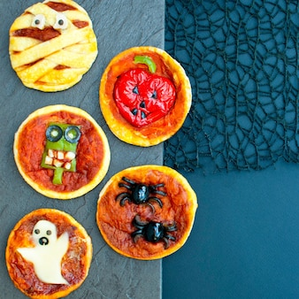Mini pizza de comida de halloween com azeitonas de queijo e ketchup comida maluca engraçada para crianças
