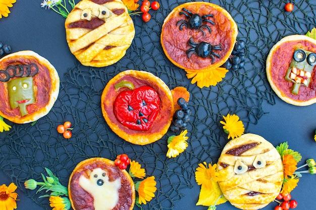 Mini pizza de comida de halloween com azeitonas de queijo e ketchup fantasma de múmia decorada