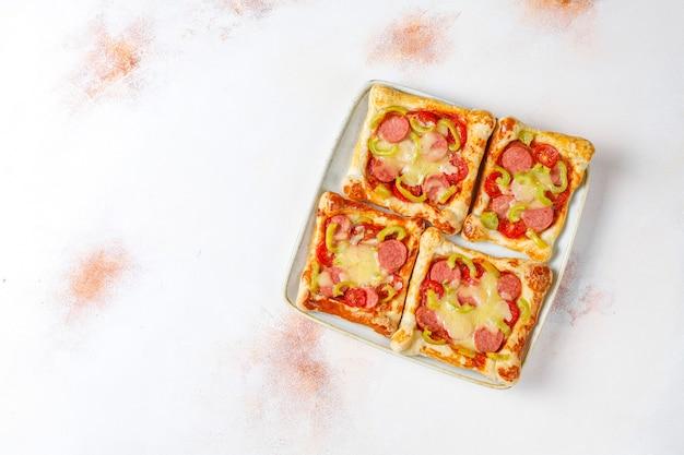 Mini pizzas de massa folhada com enchidos.