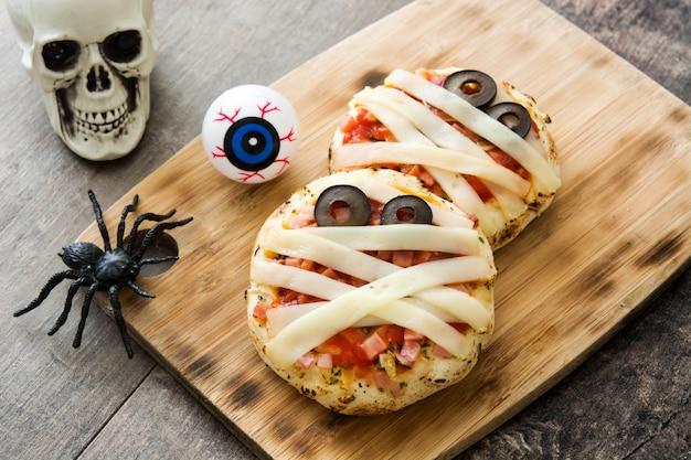 Mini pizzas de múmias de halloween na mesa de madeira