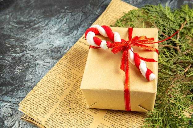 Mini-presente de vista inferior amarrado com fita vermelha doce de natal em jornal em fundo cinza