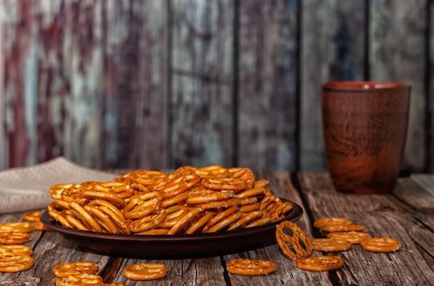 Mini pretzels com sal em uma tigela com fundo de madeira. foco seletivo.