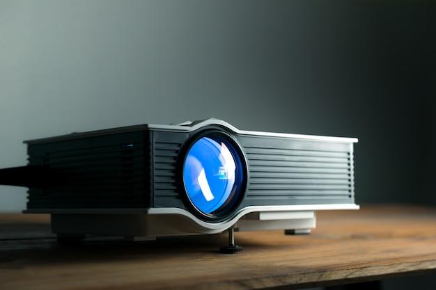 Mini projetor conduzido na tabela de madeira em um conceito do cinema em casa do projetor da sala.