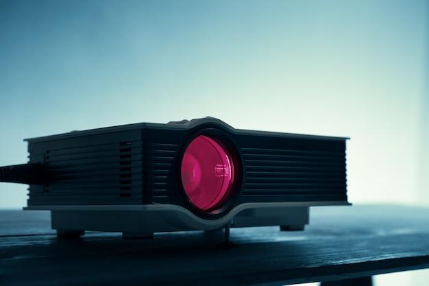 Mini projetor conduzido na tabela no fundo escuro do cinema em casa do projetor do tom de blude.