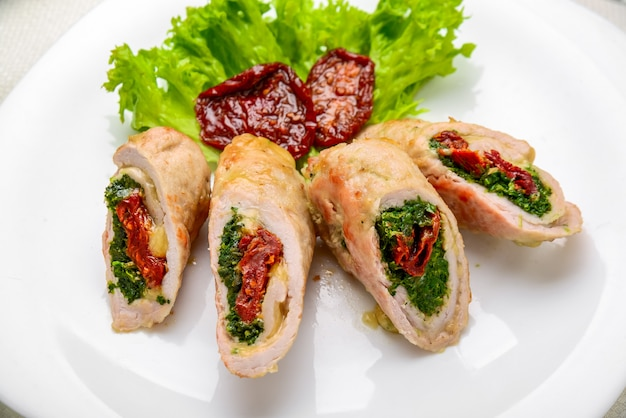 Mini rolos de frango com tomate seco e espinafre. prato festivo.
