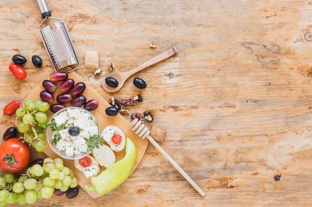 Mini sanduíches com ralador, colher e mel gotejador na mesa