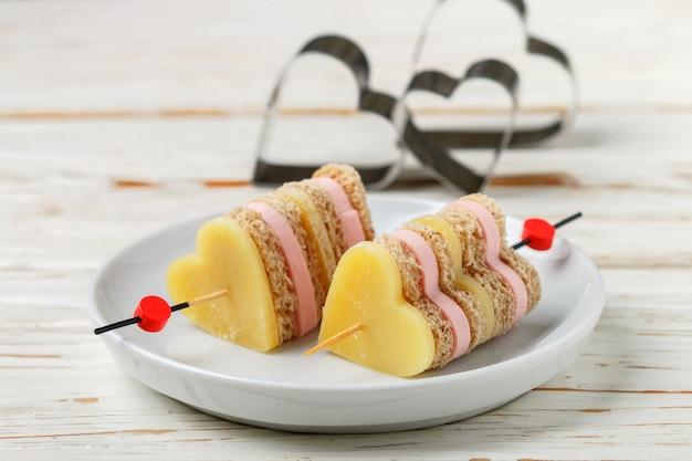Mini sanduíches queijo parmesão presunto pão no espeto em forma de coração,