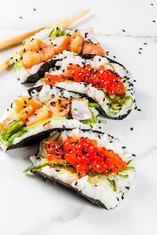 Mini sushi-tacos, sanduíches com salmão, hayashi wakame, daikon, gengibre, caviar vermelho.