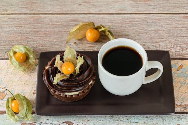 Mini tarte com creme de mascarpone e ganache de chocolate, decorada com physalis, ao lado de uma xícara de café.