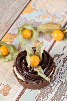 Mini tarte com creme de mascarpone e ganache de chocolate, decorada e rodeada com physalis (foto vertical).