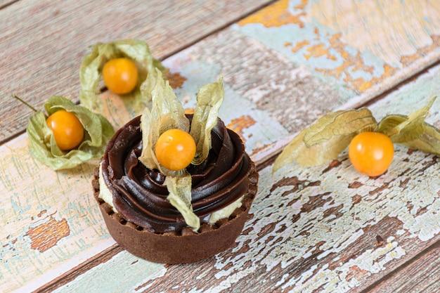 Mini tarte com creme de mascarpone e ganache de chocolate, decorada e rodeada de physalis.