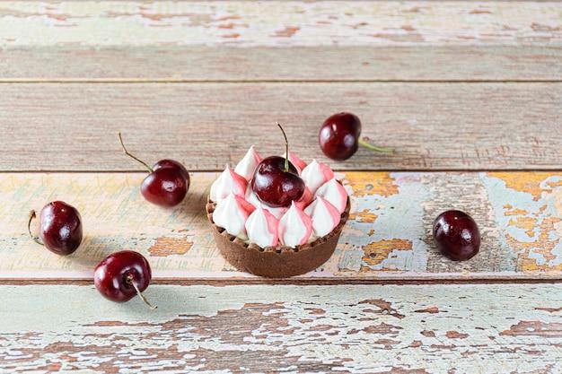 Mini tarte de chocolate com ganache de chocolate, com cobertura de natas batidas e cereja. cercado por cerejas.