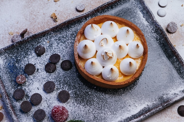 Mini tartelete com geleia de frutas e merengue tarte com merengue italiano e creme no prato preto sobremesa caseira lindo café da manhã