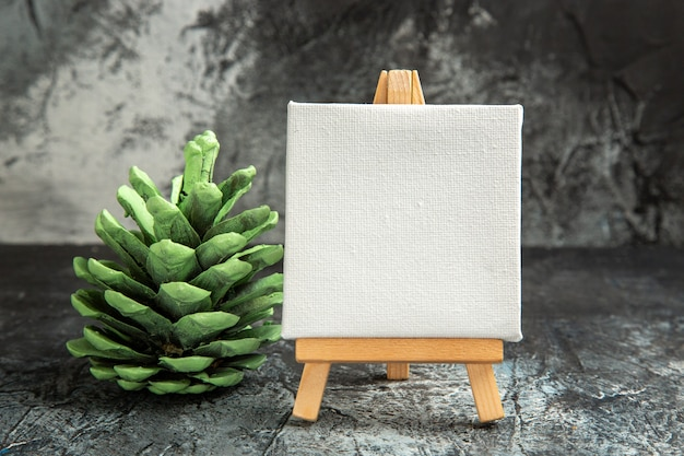Mini tela branca de vista frontal com pinha verde de cavalete de madeira em fundo escuro isolado