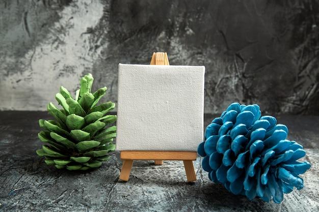 Mini tela branca de vista frontal com pinhas coloridas cavalete de madeira no escuro