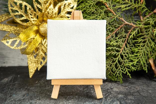 Mini tela de vista frontal em cavalete de madeira, ramo de pinho, enfeite de natal em fundo cinza