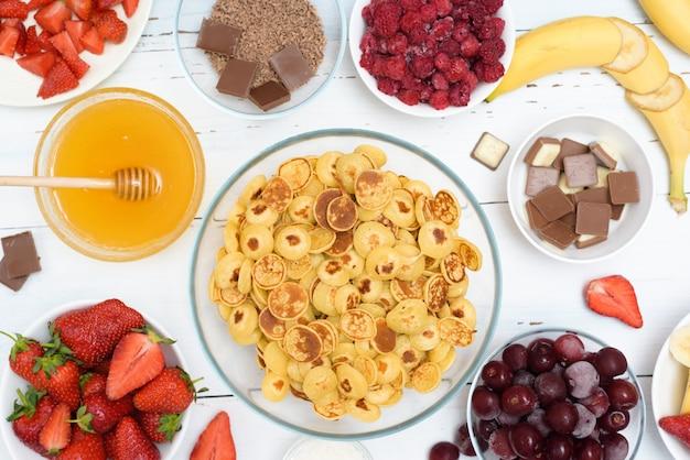 Mini tigela de cereal de panqueca com morangos frescos, banana, chocolate, raspas de coco e mel em pequenos pratos.