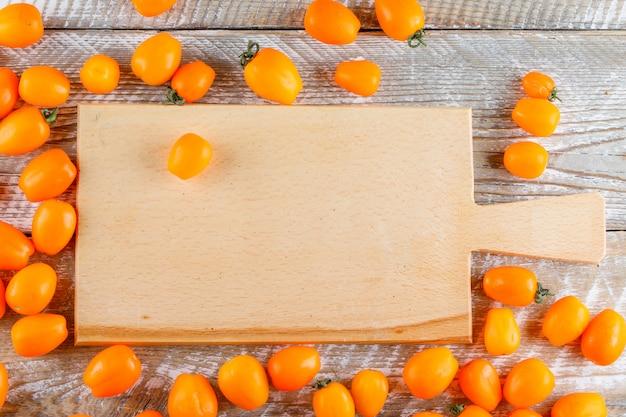 Mini tomates amarelos na placa de madeira e de corte. configuração plana.