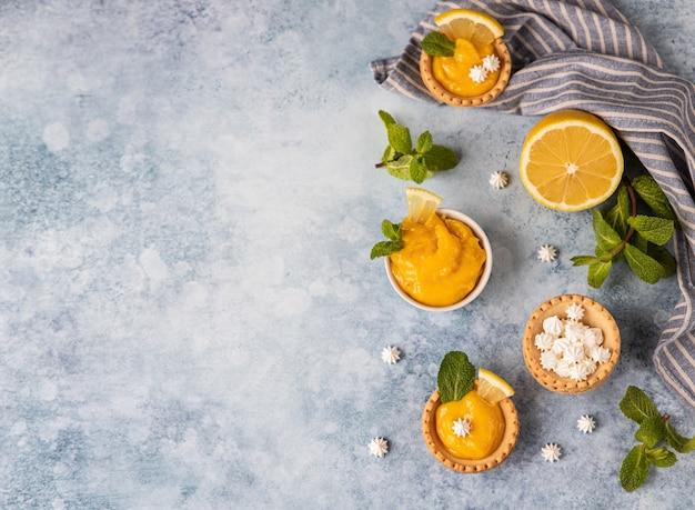 Mini tortas com coalhada de limão, mini merengue rodelas de limão e hortelã sobre fundo azul de concreto