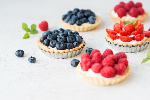 Mini tortas com natas e frutas vermelhas para sobremesa, cestas com mirtilos e framboesas