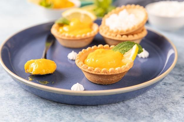 Mini tortas de coalhada de limão decoradas com hortelã e rodelas de limão em um prato de cerâmica azul.