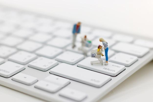 Miniatrue pessoas, compradores com carrinho de compras em pé no teclado