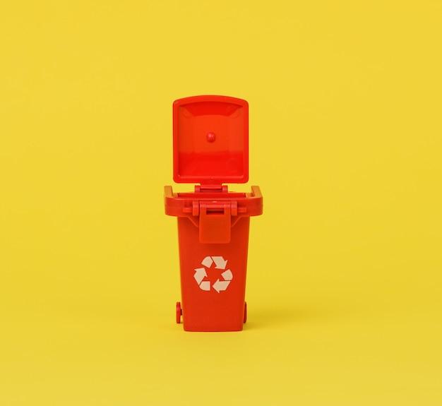 Miniatura da lixeira de plástico vermelho na superfície amarela, close-up