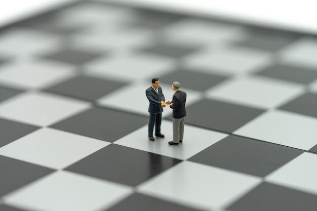 Miniatura de 2 pessoas de negócios agite as mãos em um tabuleiro de xadrez com uma peça de xadrez