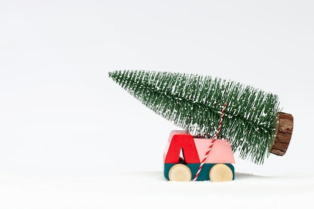 Miniatura de carro carregando uma árvore de natal