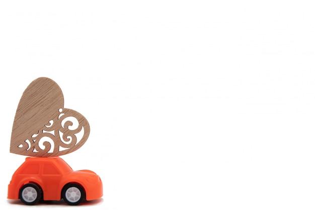 Miniatura de carros rosa e amarelos carregando almofadas de coração. conceito mínimo.