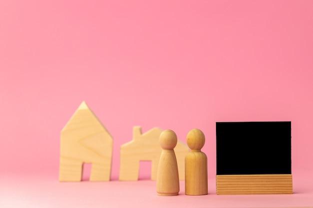 Miniatura de casa de madeira e pessoas de brinquedo em fundo rosa close-up