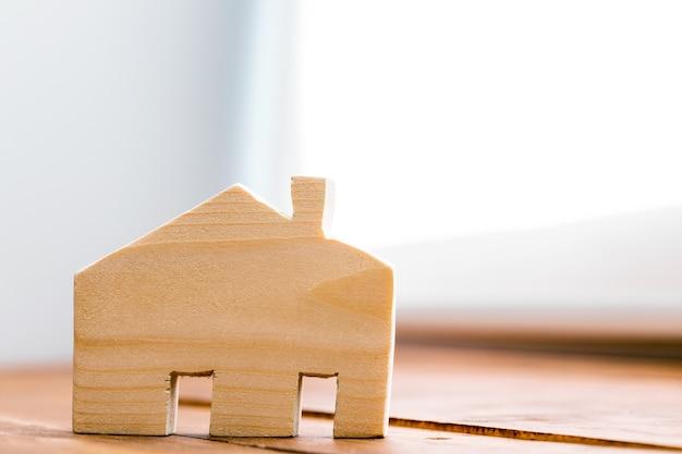 Miniatura de casa de madeira na superfície de madeira close-up foto