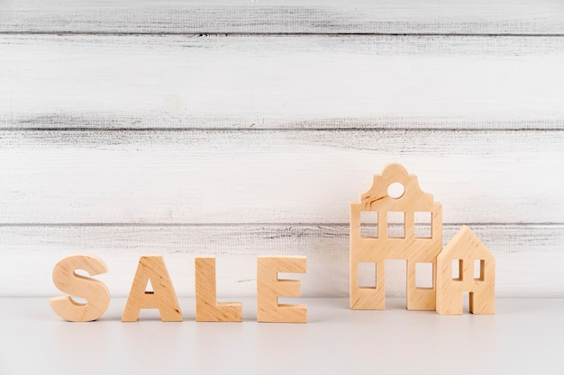 Miniatura de casa e letras de venda de madeira