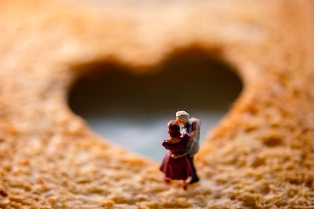 Miniatura de casal de idosos sênior no pão torrado queimado fatiado com uma forma de coração