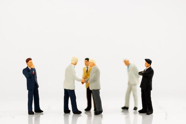 Miniatura de empresários aperto de mão com parceria