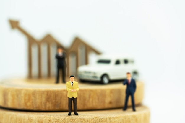 Miniatura de empresários de pé na pilha de moedas com gráfico e carro