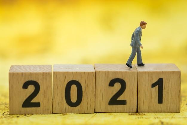 Miniatura de empresários, pessoas caminhando sobre uma pilha de blocos de madeira número 2021
