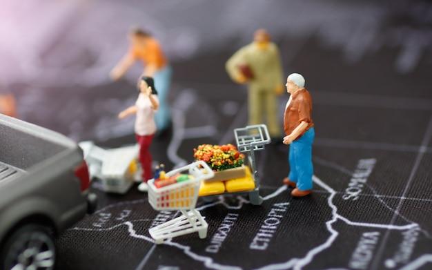 Miniatura de família com carrinho de compras e pegar o carro no mapa