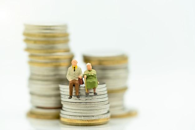 Miniatura de felizes idosos em pé na pilha de moedas